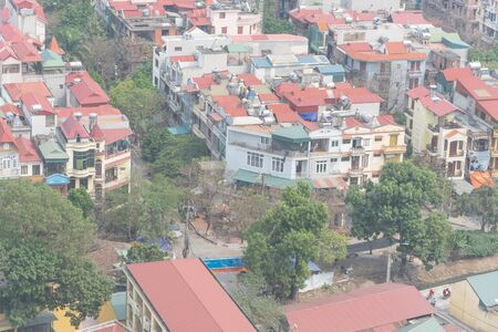 Close-up aerial view residential neighborhood near downtown Hanoi, Vietnam with dense of multistory house with red metal roof. Typical suburb house with small alley and compact lot size. Фото со стока