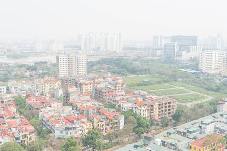 Dense of residential houses and high-rise condominium building in background. Foggy or polluted air is common in Hanoi, Vietnam. Aerial view urban sprawling with red metal roof multistory homes. Stock Photo