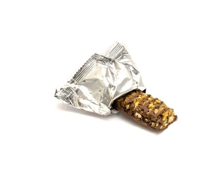 Dark chocolate nutrition bar plastic wrap opened isolated on white. Natural ingredients are almond, cashew, coconut, nuts, cocoa coating of sugar, palm kernel oil, organic sunflower lecithin, sea salt