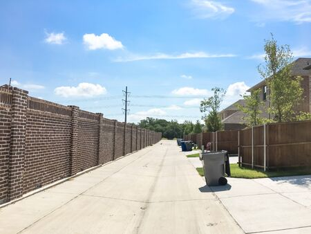 Clean back alley of new development neighborhood in Allen, Texas, America under cloud blue sky. Two story house with wooden fence and brick wall screen and row of trash and recycle bins.