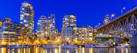 Panorama view reflection of Vancouver BC skyscraper and Granville Bridge along False Creek at blue hour evening. Moored boats in downtown yacht harbor marina