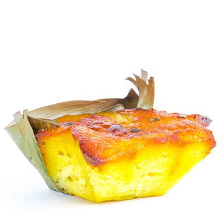 Half cut Bibingka, traditional Philippines cake isolated on white background. A Filipino baked rice with butter and cheese in banana leaves, usually eaten for breakfast, especially during Christmas season