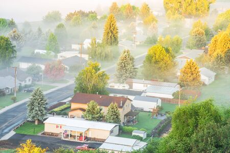 Misty spring landscape with foggy and first ray of early morning light. Aerial view of small valley town at rural of Colfax, Eastern Washington, US surrounded by morning fog, pine trees and empty road