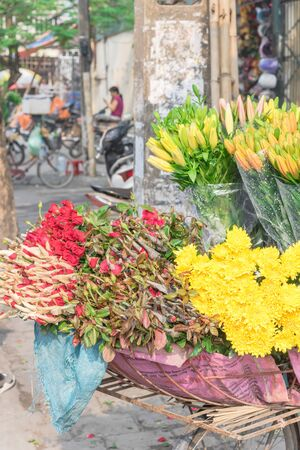 Fresh cut boutiques Chrysanthemum, rose and water lily arranged on bicycle street vendor in Hanoi, Vietnam. Close-up mobile flower shops on the bike.