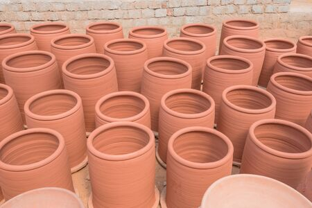 Top view plain terracotta vases at pottery shop near Hanoi, Vietnam. Handmade containers with sauces display for sun dry near brick wall.