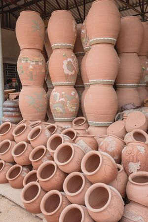 Close-up stacked of ancient terracotta vases at pottery shop near Hanoi, Vietnam. Handmade container with different shapes and sizes inside metal roof steel structure warehouse ready to sell