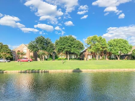 Riverside residential neighborhood in suburbs Dallas, Texas, USA. Row of single family detached homes with parked car on street, mature oak trees, high stone retaining wall, green grass lawn, blue sky 免版税图像 - 142533772