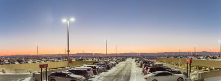 Panorama view full terminal parking at Denver International Airport (DIA) in frosty cold autumn sunset. Row of cars at busy lot with snowdrifts during severe weather condition in Colorado, USA