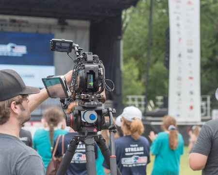 Rear view head of video operator with cap operating professional camcorder record live event with blurry audience background. Video camera with external monitor noise cancelling stereo microphone
