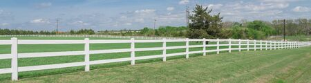 Panoramic long wooden white fence to horizontal line in cloud blue sky at farmland in Ennis, Texas, USA