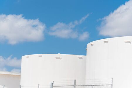 Close-up white oil storage tank under cloud blue sky in Corpus Christi, Texas, America. Large industrial container for petrol, oil, natural gas. Tank farm at petrochemical, oil refinery plant