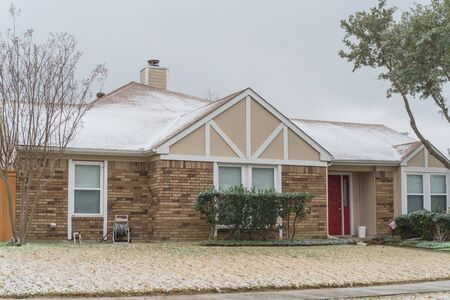 Typical bungalow house under winter snow cover near Dallas, Texas. Middle class residential home in America. Archivio Fotografico