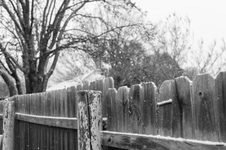 Wooden fence picket and posts under snow covered at residential area suburbs Dallas, Texas, USA