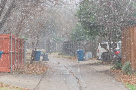 Light snowing over back alley of residential neighborhood suburbs Dallas, Texas, USA