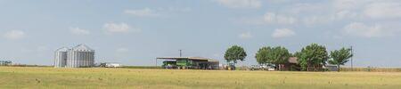 Panoramic Texas farm house with large storage tower silo in farmyard prairie