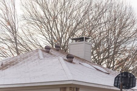 Chimney on frost covered black shingle roof of residential house near Dallas, Texas, America. Light frosted roof surrounded by bare trees