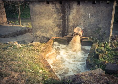 Typical Asian irrigation pumping system with bubbles flowing on water running from a rustic pipeline in Vietnam