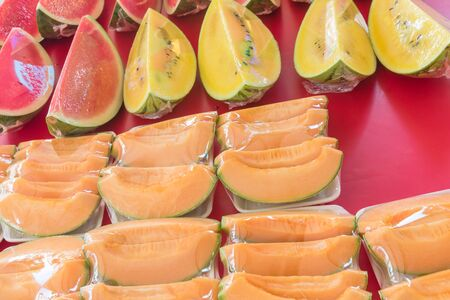 Variety of cantaloupe, red and yellow watermelon slices in plastic wrap polystyrene  trays at fruit stall
