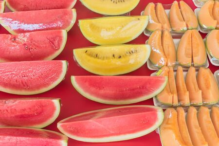 Variety of cantaloupe, red and yellow watermelon slices in plastic wrap polystyrene trays at fruit stall in Singapore