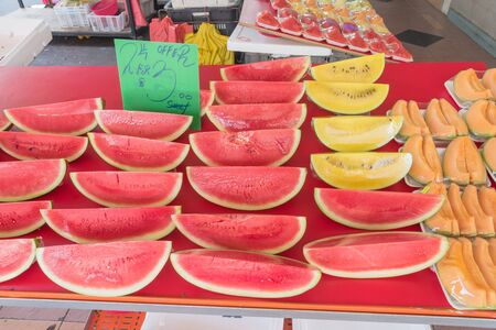 Mix of red, yellow watermelon and cantaloupe slices in cling films at street market stand in Singapore