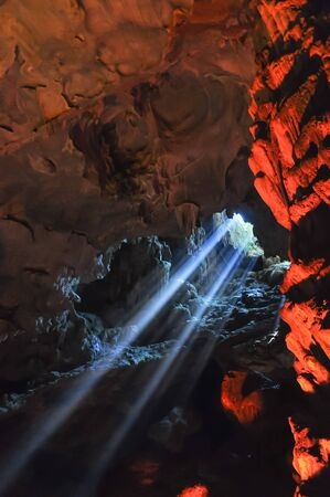 Colorful sun light rays shining into cave in Halong Bay Stock fotó