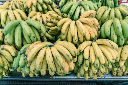 Organic green and natural ripening banana bunches at fruit stand in Geylang, Singapore