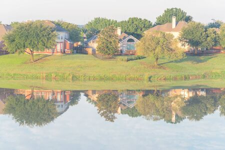 Two-story bungalow houses reflection on idyllic lake at suburban neighborhood near Dallas, Texas, USA