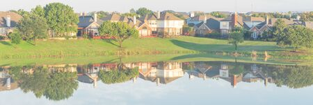 Panoramic view lakeside residential neighborhood row of houses mirror reflection near Dallas, Texas, USA