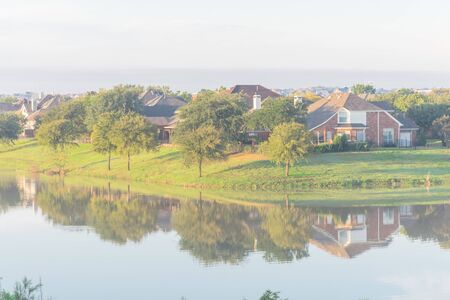 Top view suburban houses reflection on tranquil lake at residential area near Dallas, Texas, USA