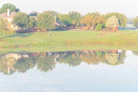 One story bungalow houses reflection on idyllic lake at suburban neighborhood near Dallas, Texas, USA