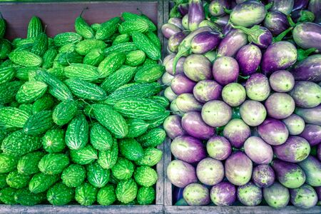 Filtered image vibrant green bitter melon and purple Asian eggplants at vegetable stand in Little India, Singapore 免版税图像