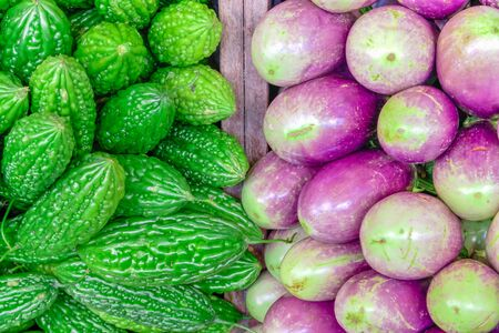 Close-up bitter melon and purple Asian eggplants at local market stand in Little India, Singapore