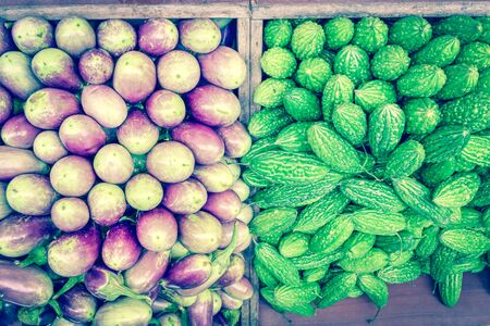 Vibrant green bitter melon and purple Asian eggplants at vegetable stand in Little India, Singapore 版權商用圖片