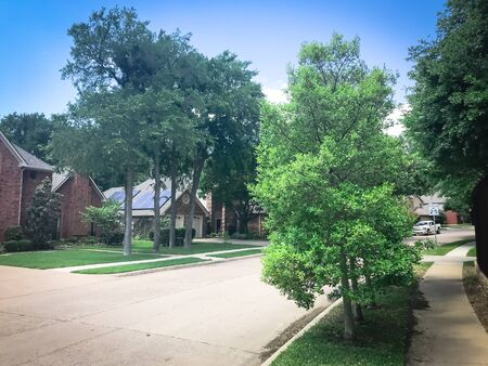 Lush green sidewalk pathway in residential area in suburban Dallas, Texas, USA and solar roof house