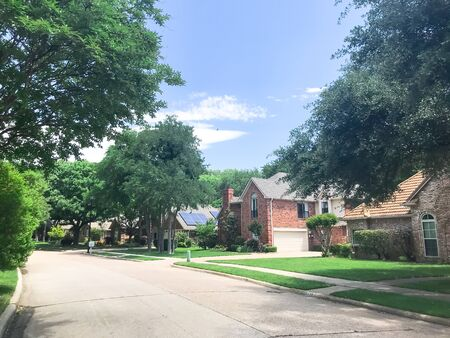 Clean and green residential street with row of upscale house and solar panel roof surrounded by tall trees near Dallas, Texas, USA