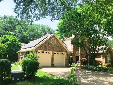 Typical single family house in suburbs Dallas, Texas, USA with solar panel roof surrounds by tall trees 版權商用圖片