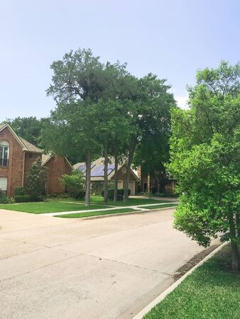 Upscale suburbs residential area with solar panel roof house and tall trees near Dallas, Texas, USA