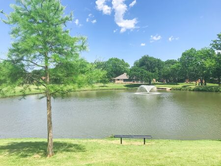 Picnic bench looking at clear pond with floating decorative water fountain at local park in Coppell, Texas, USA