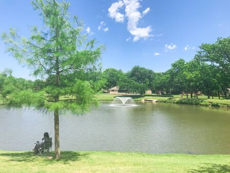 Asian lady on folding picnic chair under shading tree fishing at residential park with floating fountain in Coppell, Texas, USA