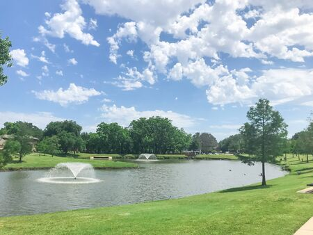 Two floating fountains at residential park with clean pond surrounded by large trees in Coppell, Texas, USA 版權商用圖片