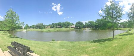 Panorama view residential park with double water fountains on clear pond, pathway and picnic bench under sunny blue cloud sky in Coppell, Texas, USA. Unidentified people fishing and feeding ducks 版權商用圖片