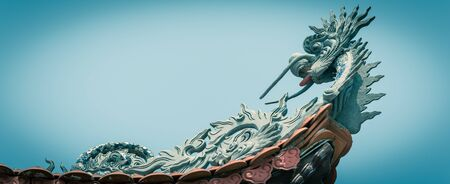 Panoramic upward view typical cornice roof with dragon head sculpture and red tile roof in Vietnam
