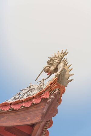 Upward view typical cornice roof with dragon head sculpture and red tile roof in Vietnam 版權商用圖片