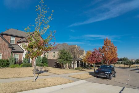 Typical front porch entrance of new suburban houses with parked car on colorful fall street outside Dallas, Texas, USA