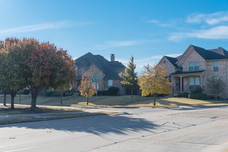 Quite new development subdivision with row of suburban houses and colorful fall foliage along sidewalk near Dallas, Texas, USA