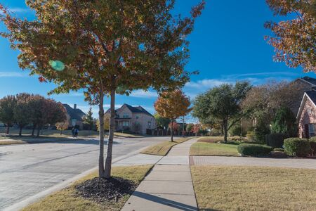 Clean neighborhood street with colorful fall foliage and unidentified people taking a morning stroll suburbs Dallas, Texas, USA