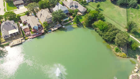 Flyover waterfront and park side houses with lake fountain in sunny day near Dallas, Texas, USA