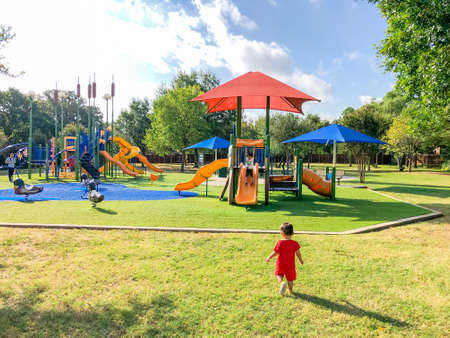Rear view Asian toddler boys playing at neighborhood playground with sun shade sails in Flower Mound, TX, US Archivio Fotografico