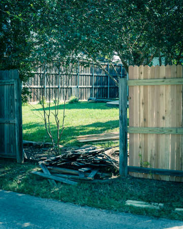 Filtered image aged wooden fence near new lumber boards installation of suburban residential house in Texas, USA Imagens