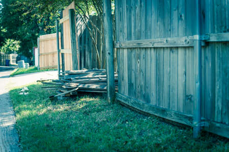 Filtered image aged wooden fence near new lumber boards installation of suburban residential house in Texas, USA Foto de archivo
